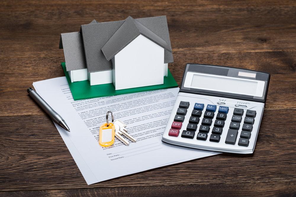 Lejekontrakt med figur af et hus og nogle nøgler, ved siden af en lommeregner