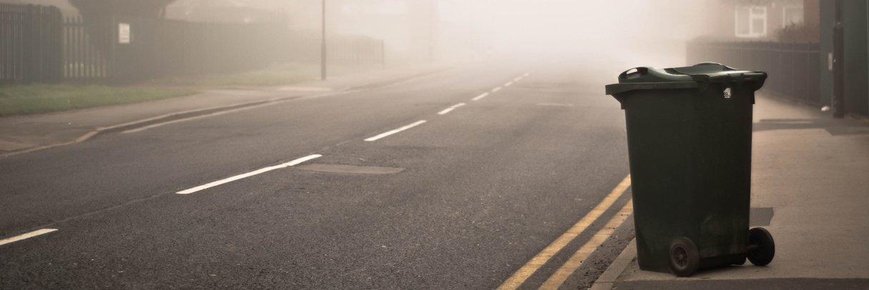 Vuilnisbak op een mistige weg