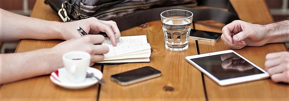 Twee mensen plannen met behulp van een notaboek, telefoons en tablet