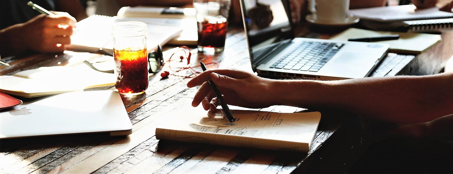 Tafel met computers, nota's en pennen