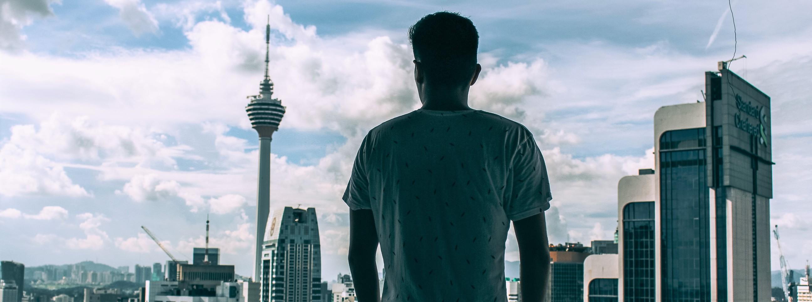 Man kijkt naar skyline Kuala Lumpur in Maleisië
