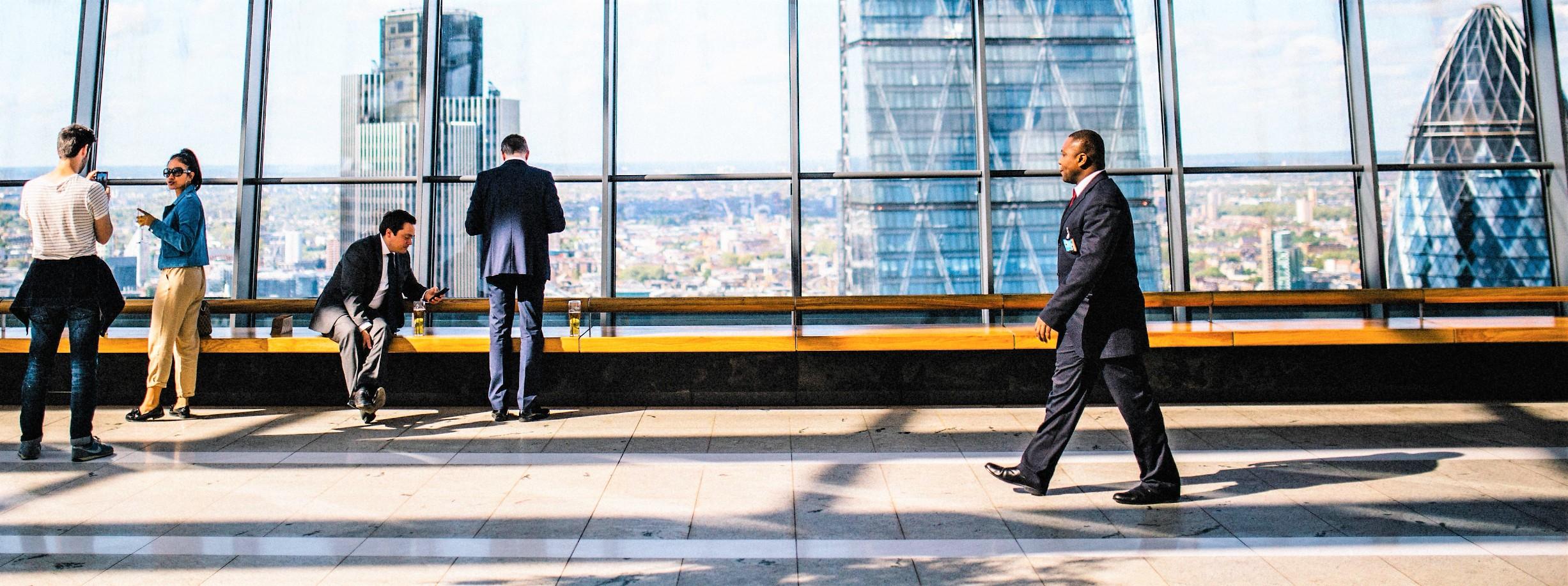 Mensen in kantoorgebouw met zicht op de Gherkin Tower in Londen