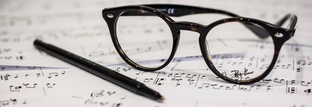 Bril en pen op bladmuziek