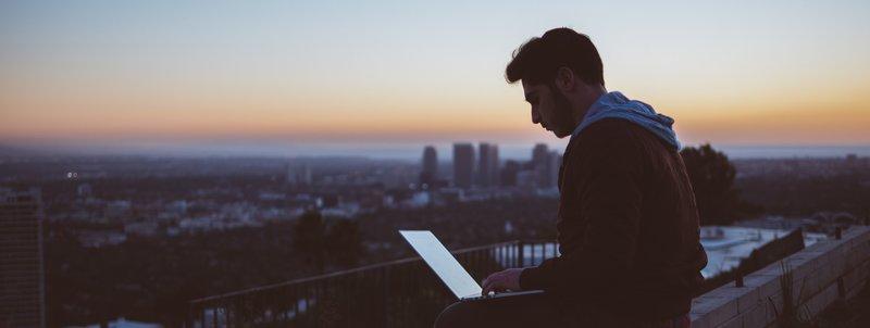 Man met laptop en skyline in de achtergrond