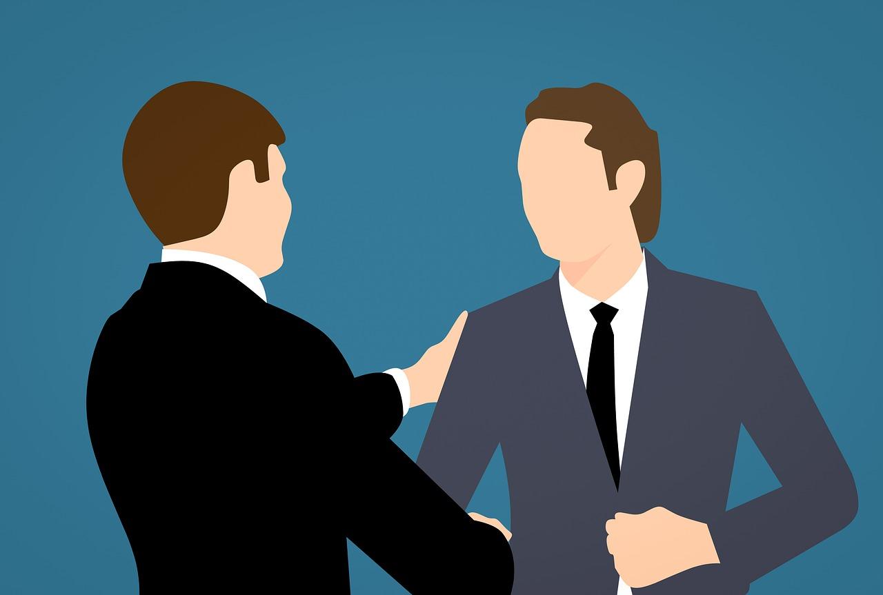 To mænd, der siger farvel ved en afskedigelse. De er begge iført jakkesæt og giver et formelt håndtryk