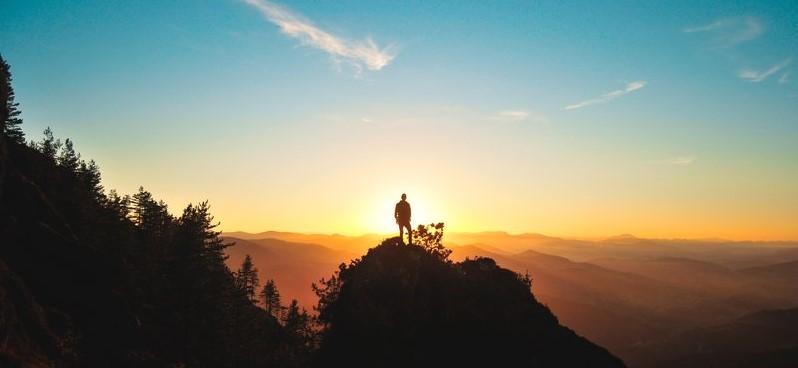 Man kijkt vanop een heuvel naar de zonsopgang