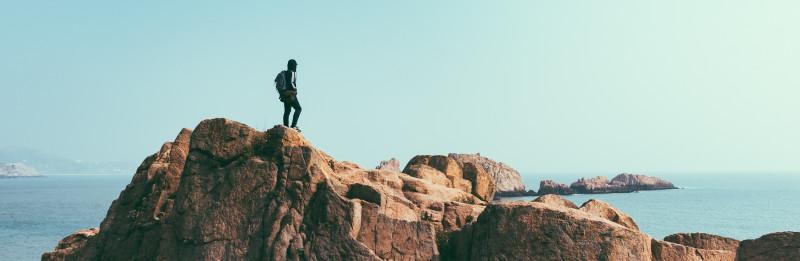 Man kijkt uit over berglandschap en zee