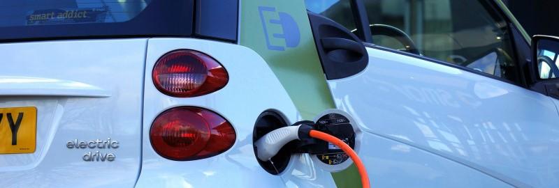 Een voorbeeld van duurzaam ondernemen: een elektrische auto die opgeladen wordt aan een laadpaal