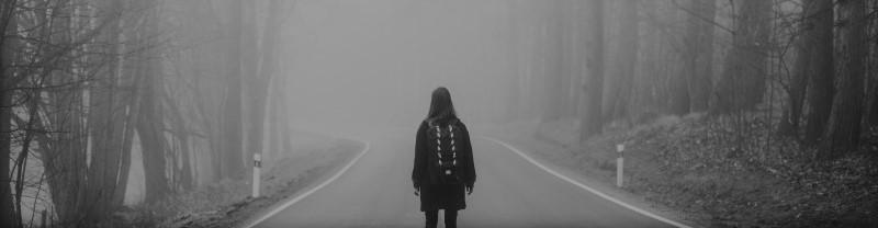 Meisje op een mistig pad doorheen het woud