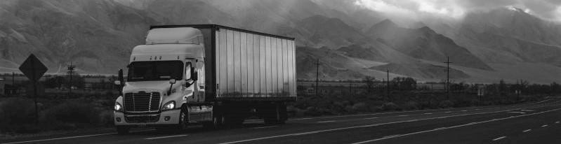 Een vrachtwagen rijdt door een bergachtig landschap