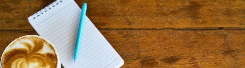 Notaboekje met blauwe pen en een kop koffie