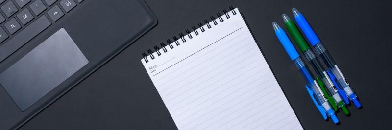 Computer, notitieboekje en drie pennen