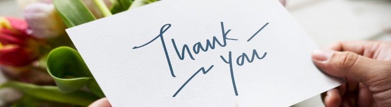 """Een kaartje met """"Thank you"""" erop en bloemen in de achtergrond"""