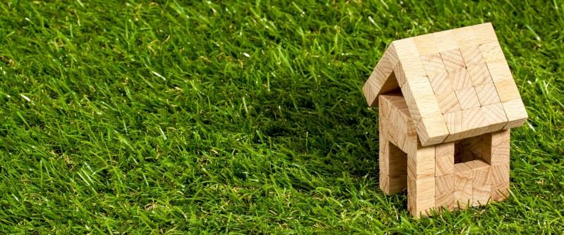 Een houten speelgoedhuisje in het gras