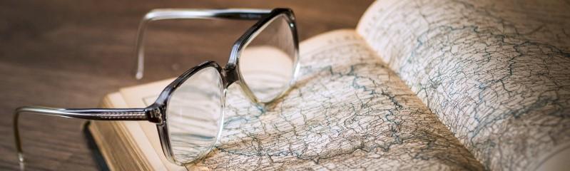 Een bril rust op een vergeelde landkaart