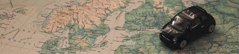 Een speelgoedautootje rijdt over de kaart van Europa