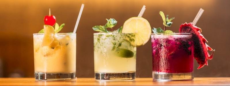 Drie kleurrijke cocktails op een rij