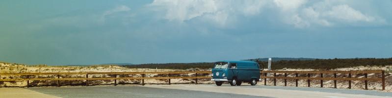 Een VW-busje op een verlaten, zonnige parking