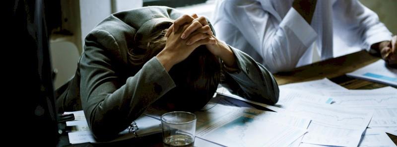 Een medewerker die gestresseerd het hoofd buigt