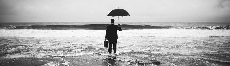 Een zakenman met paraplu en beide voeten in de oceaan