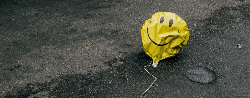 Een gekreukte smiley-ballon op straat