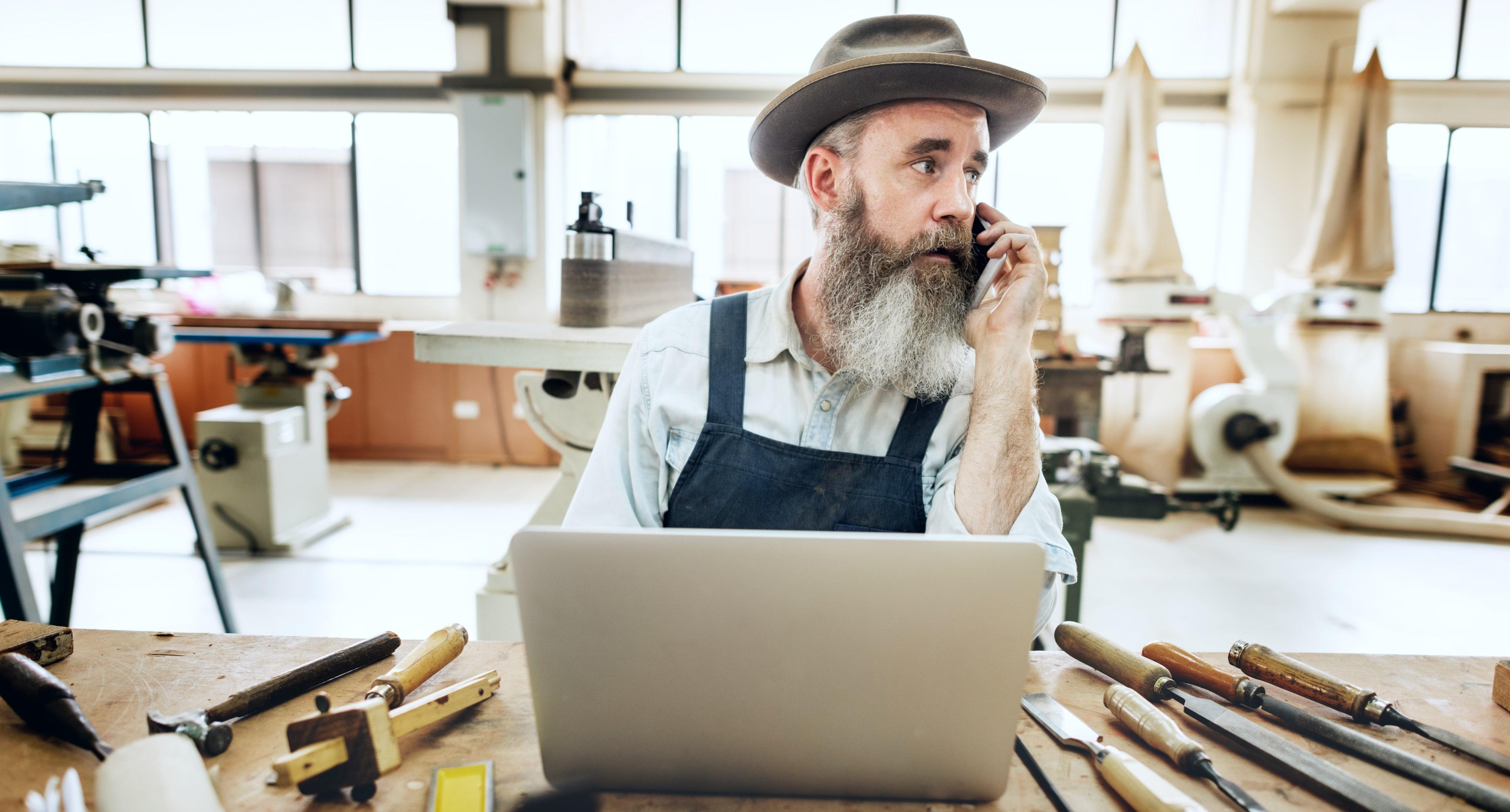 Håndværker med mobiltelefon og pc