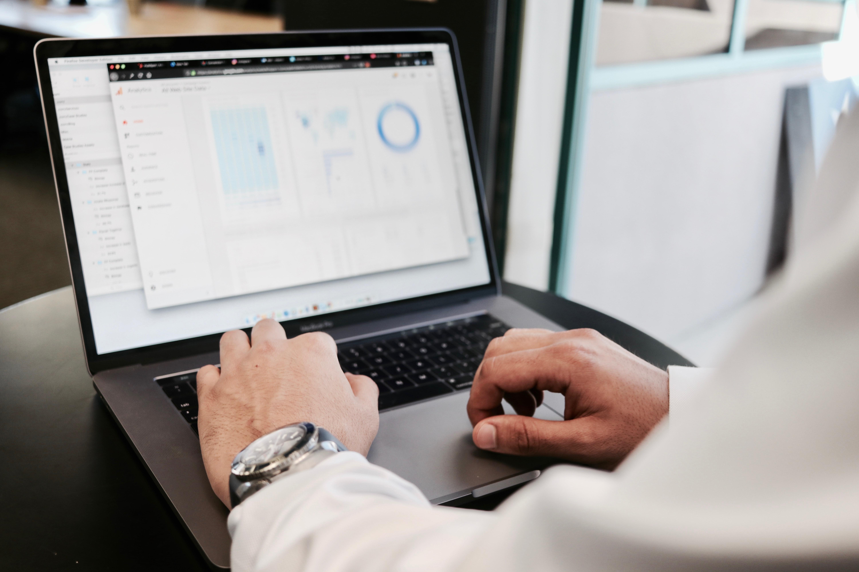 Mand indberetter moms og afregner, så han kan undgå momskarrusellen. Manden sidder ved en grå computer og har en hvid skjorte og et stort ur på.